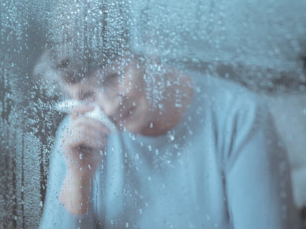 A woman is crying while looking outside her bedroom due to memory loss