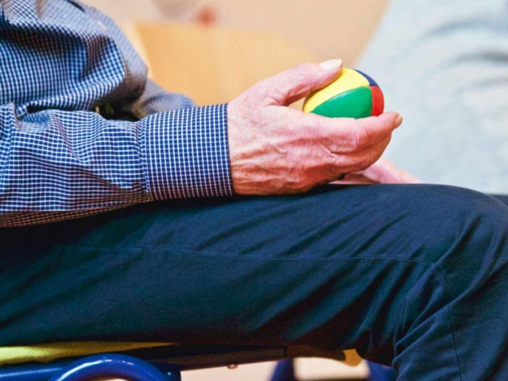 an elderly patient in physical therapy is holding a small colorful ball