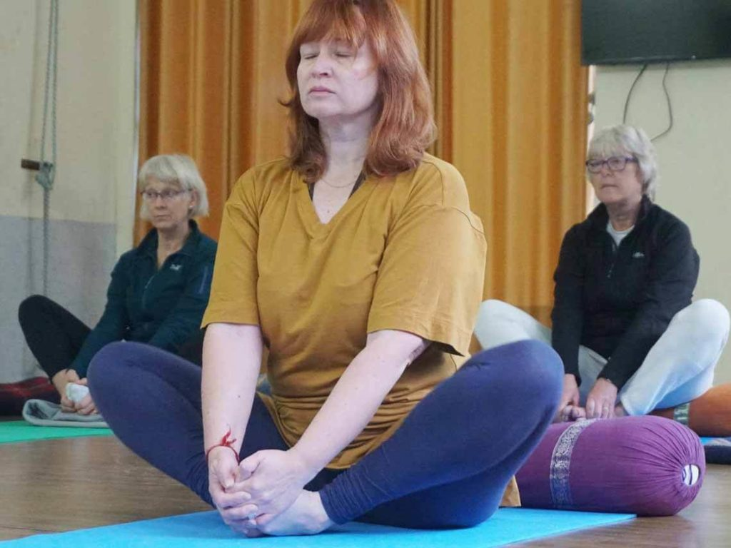 Three older females are doing a yoga session to help with their post-acute care